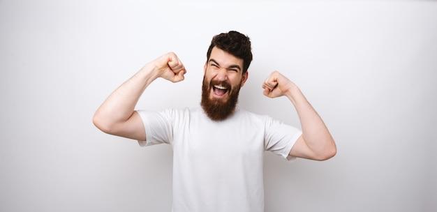 Giovane uomo barbuto attraente che fa un gesto del vincitore con le sue braccia su priorità bassa bianca.