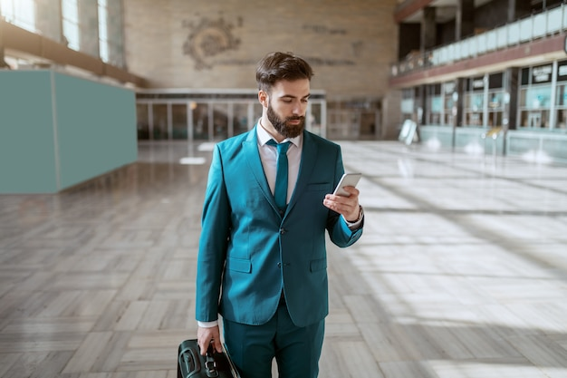 Giovane uomo d'affari serio barbuto attraente nei bagagli di trasporto del vestito blu e facendo uso dello smart phone mentre stando alla stazione ferroviaria. concetto di viaggio d'affari.