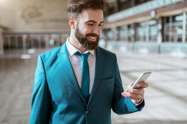 Giovane uomo d'affari sorridente barbuto attraente nei bagagli di trasporto del vestito blu e facendo uso dello smart phone mentre stando alla stazione ferroviaria. concetto di viaggio d'affari.