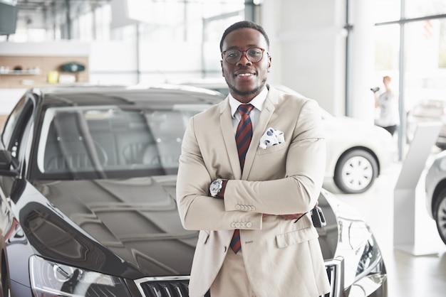 Il giovane attraente uomo d'affari nero acquista una nuova auto, i sogni diventano realtà