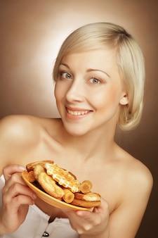 Giovane donna bionda attraente con i biscotti