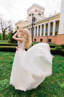 Giovane sposa bionda attraente con capelli ricci che cammina nel parco e nel sorridere