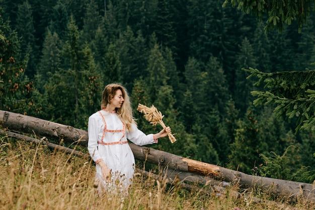 Giovane ragazza bionda attraente in vestito bianco con ricamo in posa con bouquet di spighette sul paesaggio pittoresco