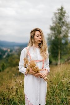 Giovane ragazza bionda attraente in vestito bianco con ornamento in posa con bouquet di spighette sul pittoresco paesaggio di campagna