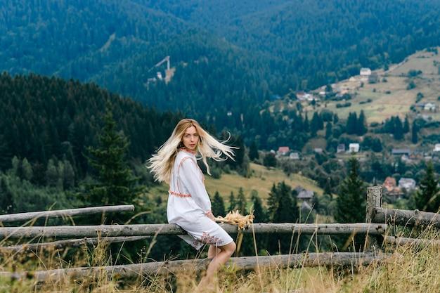 Giovane ragazza bionda attraente in vestito bianco con l'ornamento che si siede sulla staccionata in legno con bouquet di spighette sul pittoresco paesaggio di campagna