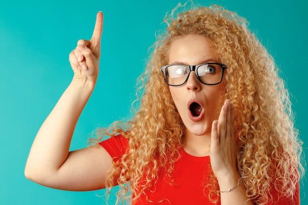 Giovane donna bionda attraente che indica il suo dito verso l'alto