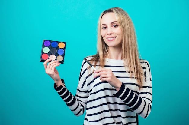 Giovane e attraente donna bionda visagiste make-up artist tiene un pennello trucco e una tavolozza di ombretti su sfondo blu in uno studio. concetto di cura della pelle e cosmetici di bellezza per il viso.