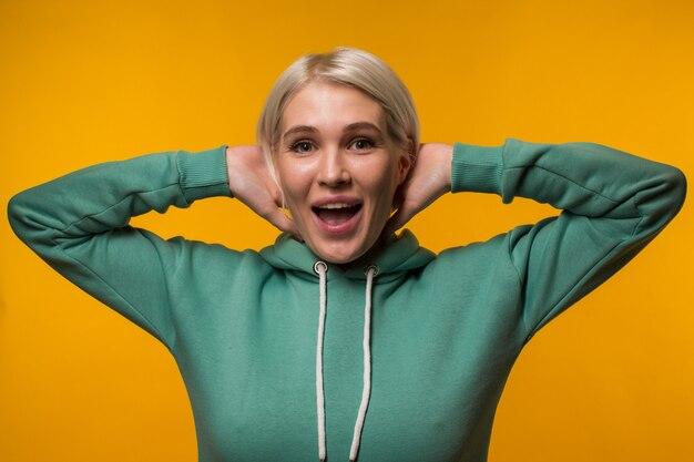 La giovane donna bionda attraente mentre la felpa con cappuccio verde rappresenta l'emozione della sorpresa