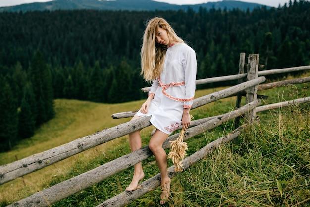 Abito bianco giovane donna bionda attraente con ornamento