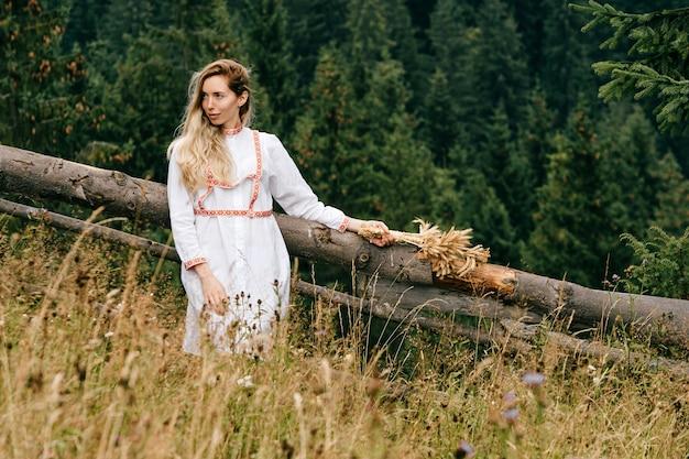 Vestito bianco dalla giovane donna bionda attraente
