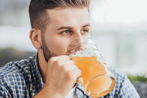 Giovane ragazzo attraente che beve birra al caffè dopo il lavoro