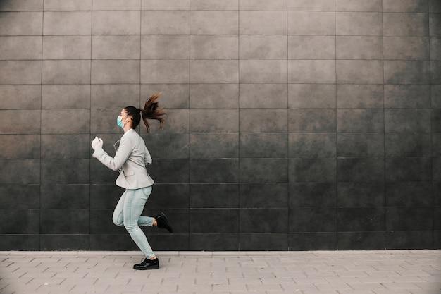 Giovane brunetta attraente vestita casual elegante con maschera facciale sul correre sul lavoro durante l'epidemia di virus corona.