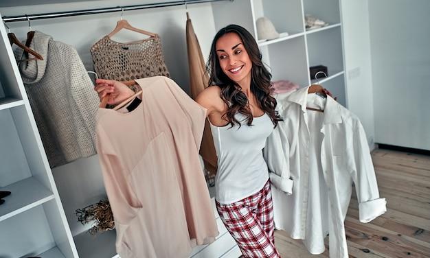 La giovane donna castana attraente sceglie i vestiti in un guardaroba a casa.