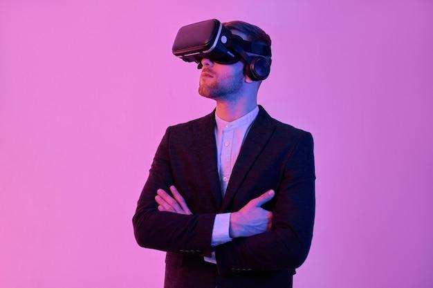 Giovane imprenditore attraente in abito nero e camicia bianca utilizza occhiali per realtà virtuale, sta con le braccia incrociate, isolato su un neon rosa