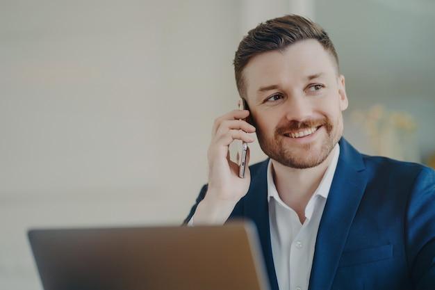 Giovane uomo d'affari attraente in abito formale che parla al telefono e sorride quando sente buone notizie. felice manager seduto in ufficio davanti al laptop e pensando ai risultati positivi della conversazione