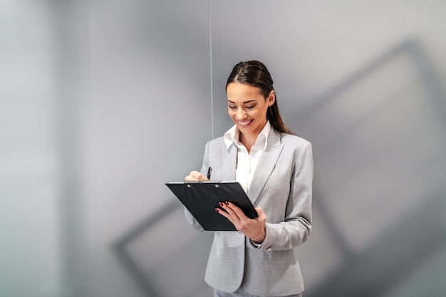 Giovane donna di affari sorridente caucasica attraente che si leva in piedi all'interno dell'azienda corporativa e che riempie i documenti sui appunti.