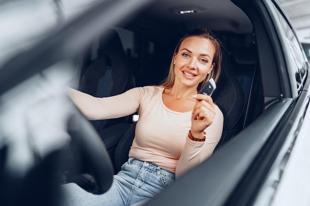 La giovane donna caucasica attraente si siede nella sua auto appena acquistata in concessionaria