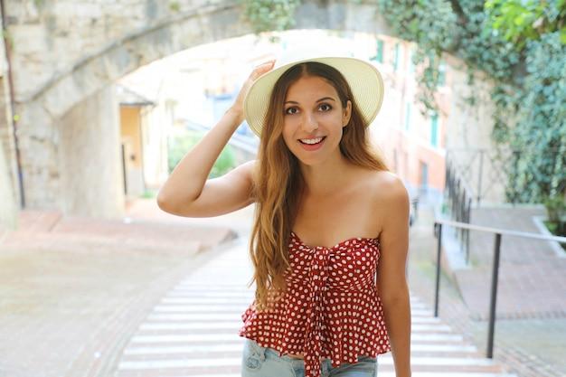 Giovane donna allegra attraente che cammina nella vecchia città italiana.