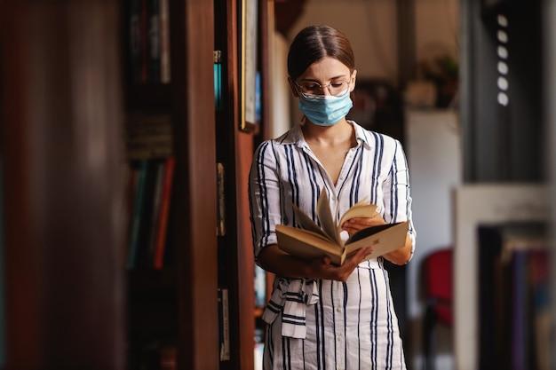 Giovane studentessa attraente con maschera facciale in piedi in biblioteca e materiale di navigazione in un libro per il progetto scolastico durante la pandemia del virus corona.