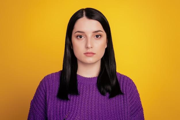 Giovane donna sicura di sé attraente in un'immagine di studio maglione viola isolata su sfondo giallo serio
