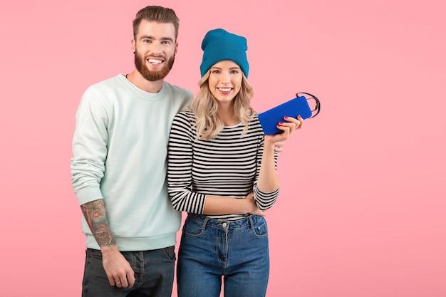 Giovani coppie attraenti che ascoltano la musica sull'altoparlante senza fili che porta l'umore positivo felice sorridente dell'attrezzatura elegante fresca che posa sul fondo rosa isolato