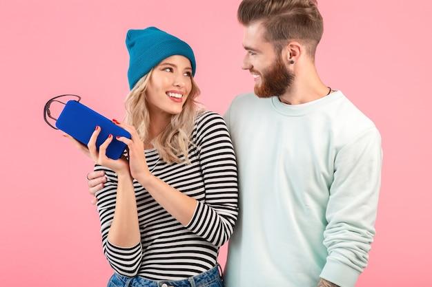 Giovani coppie attraenti che ascoltano la musica sull'altoparlante senza fili che porta l'umore positivo felice sorridente dell'attrezzatura elegante fresca che posa sulla parete rosa isolata