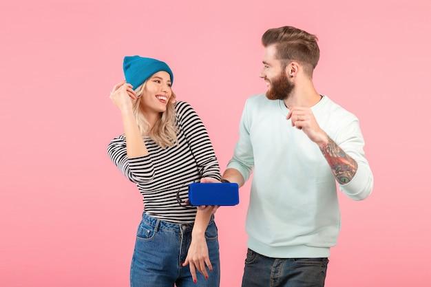 Giovane coppia attraente che ascolta la musica sull'altoparlante wireless indossando abiti eleganti e alla moda
