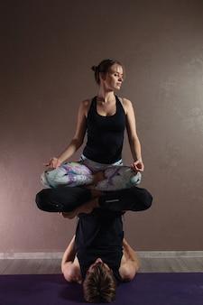 Giovani coppie attraenti che praticano yoga che indossa abiti sportivi