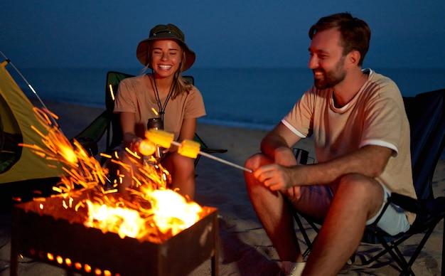 La giovane coppia attraente si siede sulle sedie pieghevoli vicino alla tenda e griglia il mais sul fuoco e si diverte a parlare di notte vicino al mare.