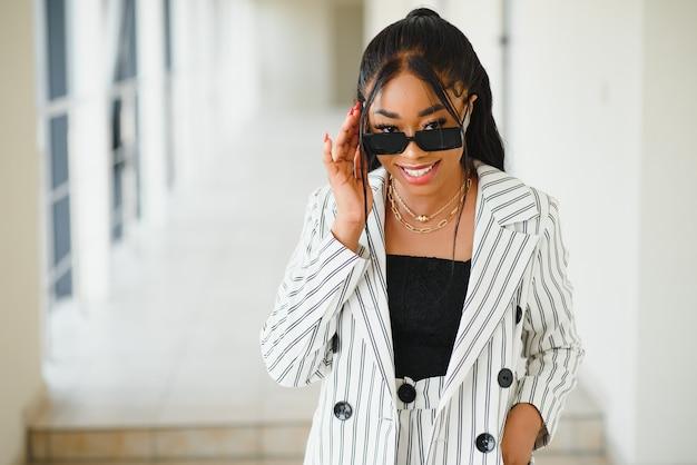 Giovane donna d'affari afroamericana elegante attraente in abbigliamento formale al corridoio dell'ufficio.