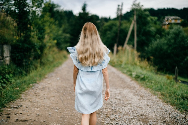 Giovane ragazza bionda elegante attraente in vestito blu che propone indietro sulla strada nella campagna