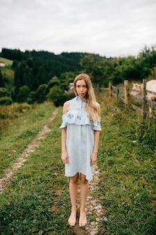 Giovane ragazza bionda elegante attraente in vestito blu che posa nella campagna