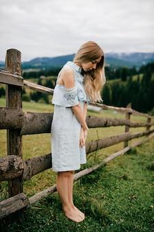Giovane ragazza bionda elegante attraente in vestito blu che posa vicino al recinto in campagna