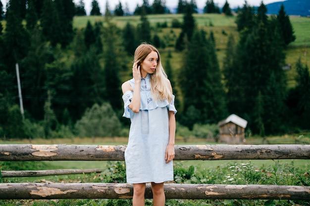 Giovane ragazza bionda elegante attraente in vestito blu che posa vicino al recinto di legno nella campagna