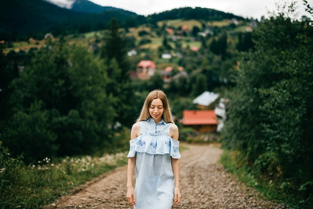 Giovane ragazza bionda elegante attraente in vestito blu che posa sulla strada nella campagna