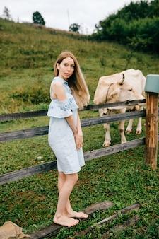 Giovane ragazza bionda elegante attraente in vestito blu che posa con la mucca nella campagna