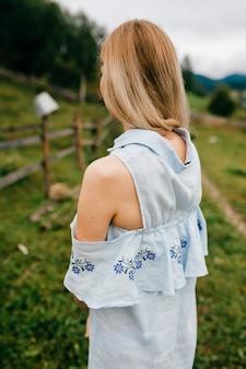 Giovane ragazza bionda elegante attraente in vestito romantico blu che propone indietro nella campagna