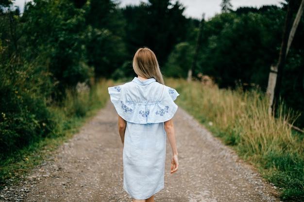 Giovane ragazza bionda elegante attraente in vestito romantico blu che propone indietro sulla strada in campagna