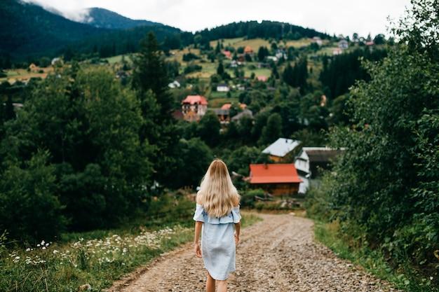 Giovane ragazza bionda elegante attraente in vestito romantico blu che propone indietro sulla strada nella campagna
