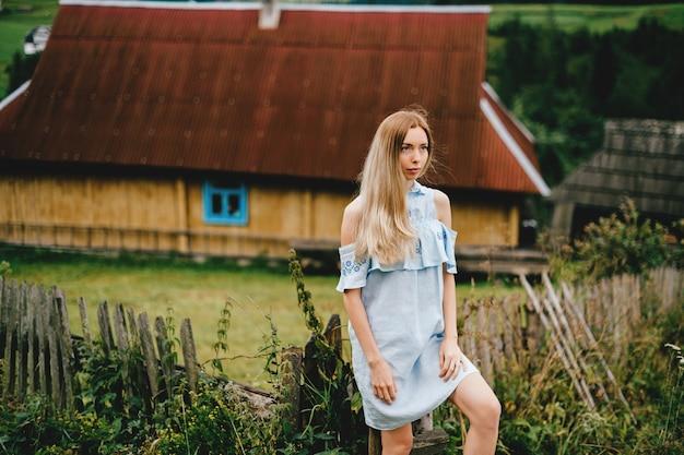 Giovane ragazza bionda elegante attraente in vestito romantico blu che posa sopra la casa di campagna in campagna