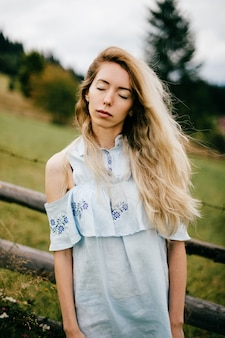Giovane ragazza bionda elegante attraente in vestito romantico blu in posa vicino al recinto in campagna