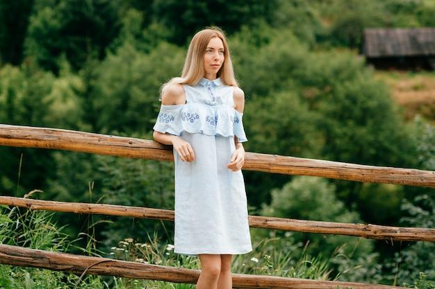 Giovane ragazza bionda elegante attraente in vestito romantico blu che posa vicino al recinto di legno nella campagna