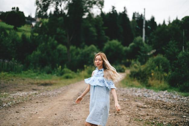 Giovane ragazza bionda elegante attraente in vestito romantico blu in posa sulla strada in campagna