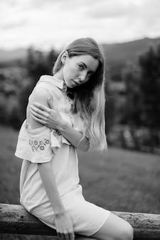 Giovane ragazza bionda elegante attraente in vestito romantico blu che si siede sulla staccionata in legno in campagna