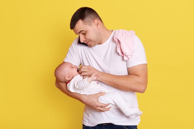 Il giovane padre attraente dà il manichino del bambino mentre parla al telefono con qualcuno, bel ragazzo che indossa la maglietta bianca che si prende cura di sua figlia infantile contro il muro giallo.