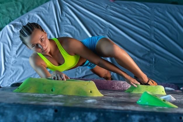 Giovane scalatore femminile attraente in un centro di addestramento che pratica intenzionalmente scalare una roccia