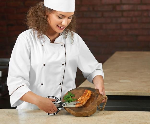 Giovane cuoca attraente che lavora al ristorante che taglia carne alla griglia con le forbici.