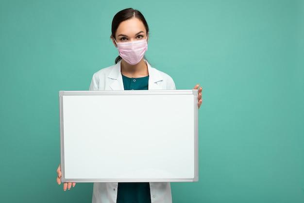 Giovane dottoressa attraente in maschera protettiva e camice medico bianco che tiene una lavagna magnetica vuota