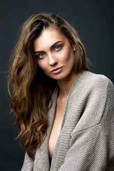 Giovane modello femminile attraente che posa in un ritratto di bellezza dello studio