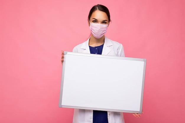 Giovane infermiera femminile attraente in maschera protettiva che tiene una lavagna magnetica vuota isolata su sfondo rosa.